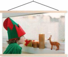 TextilePosters Kleine babyjongen in elfkostuum die door het raam naar de vallende sneeuw kijkt schoolplaat platte latten blank 120x80 cm - Foto print op textielposter (wanddecoratie woonkamer/slaapkamer)