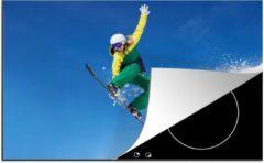 KitchenYeah Luxe inductie beschermer Snowboarden - 78x52 cm - Een jonge vrouwelijke snowboarder springt vanaf een rots - afdekplaat voor kookplaat - 3mm dik inductie bescherming - inductiebeschermer