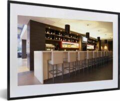 PosterMonkey Foto in lijst - Een moderne loungebar met witte barkrukken fotolijst zwart met witte passe-partout middel 60x40 cm - Poster in lijst (Wanddecoratie woonkamer / slaapkamer)