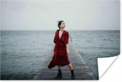 PosterMonkey Vrouw met rode jurk bij het water poster papier 60x40 cm - Foto print op Poster (wanddecoratie woonkamer / slaapkamer)
