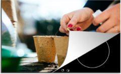KitchenYeah Luxe inductie beschermer Zaaien - 80x52 cm - Een vrouw zaait zaadjes in een bloempot - afdekplaat voor kookplaat - 3mm dik inductie bescherming - inductiebeschermer