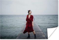 PosterMonkey Vrouw met rode jurk bij het water poster papier 120x80 cm - Foto print op Poster (wanddecoratie woonkamer / slaapkamer)