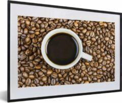 PosterMonkey Foto in lijst - Een kopje koffie wordt omringd met een berg koffiebonen fotolijst zwart met witte passe-partout middel 60x40 cm - Poster in lijst (Wanddecoratie woonkamer / slaapkamer)