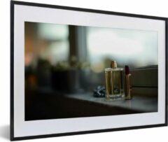 PosterMonkey Foto in lijst - Een fles parfum en lippenstift in de vensterbank fotolijst zwart met witte passe-partout middel 60x40 cm - Poster in lijst (Wanddecoratie woonkamer / slaapkamer)