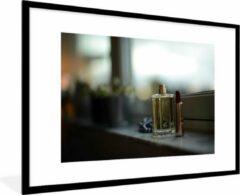 PosterMonkey Foto in lijst - Een fles parfum en lippenstift in de vensterbank fotolijst zwart met witte passe-partout groot 90x60 cm - Poster in lijst (Wanddecoratie woonkamer / slaapkamer)