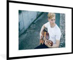 PosterMonkey Zittende gitarist bespeelt akoestische gitaar 90x60 cm