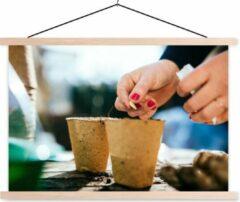 TextilePosters Vrouw zaait zaadjes in een bloempot schoolplaat platte latten blank 90x60 cm - Foto print op textielposter (wanddecoratie woonkamer/slaapkamer)