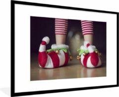 PosterMonkey Foto in lijst - Elfje draagt kerstslippers fotolijst 90x60 cm - Poster in lijst (Wanddecoratie woonkamer / slaapkamer)