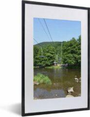 PosterMonkey Foto in lijst - Een stoeltjeslift gaat over een kleine rivier heen in de Ardennen fotolijst zwart met witte passe-partout 40x60 cm - Poster in lijst (Wanddecoratie woonkamer / slaapkamer)