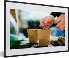 PosterMonkey Foto in lijst - Een vrouw zaait zaadjes in een bloempot fotolijst 60x40 cm - Poster in lijst (Wanddecoratie woonkamer / slaapkamer)