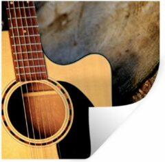 StickerSnake Muursticker Akoestische gitaar - Een akoestische gitaar op een houten ondergrond - 120x120 cm - zelfklevend plakfolie - herpositioneerbare muur sticker